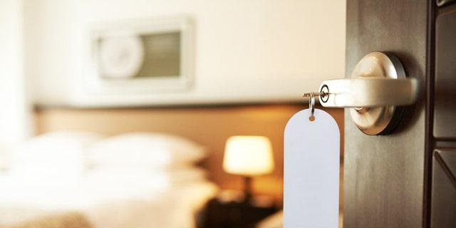Opened door of hotel room with key in the lock