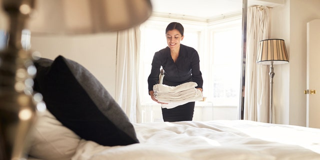 Chambermaid placing linen on hotel room bed, low angle view