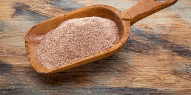 whole grain teff flour from an ancient North African cereal grass, popular in Ethiopian cuisine - a rustic scoop on wood background
