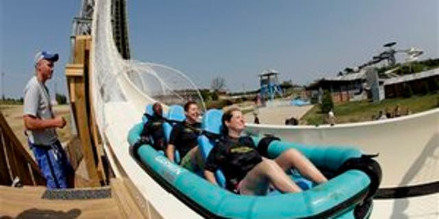 """In this photo taken with a fisheye lens, riders go down the world's tallest water slide called """"Verruckt"""" at Schlitterbahn Waterpark, Wednesday, July 9, 2014, in Kansas City, Kan. The 168-foot-tall waterslide is scheduled to open to the public Thursday, after initially being slated to open May 23. (AP Photo/Charlie Riedel)"""