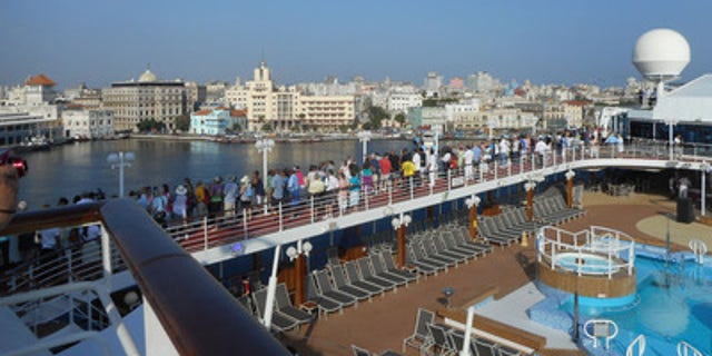 Passengers on Adonia line decks, shouting and waving to Cuban greeters on shore.
