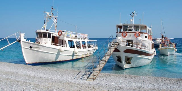 Greece, Skiathos, tourists boats with gangways moored on Lalaria beach at water's edge set against clear blue sky