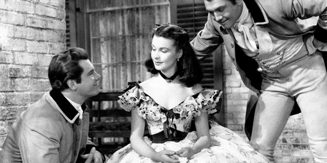 """From the left american actors Fred Crane and George Reeves, as Brent and Stuart Tarleton respectively in """"Gone with the Wind """"by Victor Fleming, court British actress Vivien Leigh, as Scarlett O'Hara, in a scene from the movie. USA, 1939. (Photo by Mondadori Portfolio via Getty Images)"""