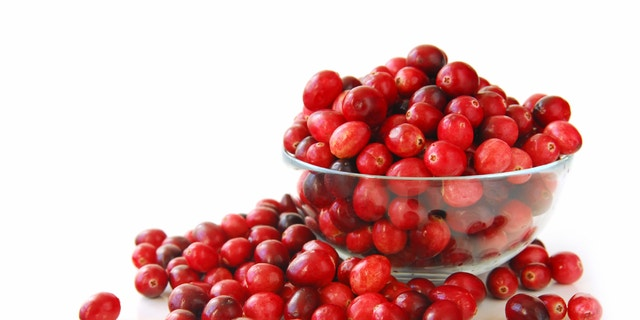 Fresh red cranberries in a glass bowl on white background