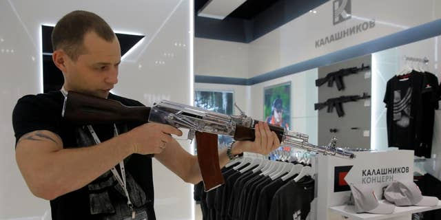 A salesperson demonstrates a model AK-47 assault rifle at the newly opened Gunmaker Kalashnikov souvenir store in Moscow's Sheremetyevo airport.