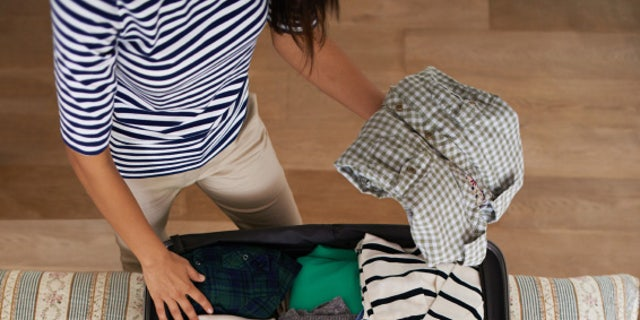 Shot of a woman packing her suitcase