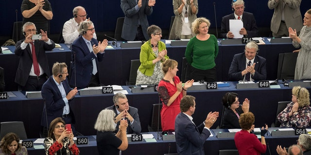 Members of the European Parliament applaud Dutch MEP Judith Sargentini, third right in green, second row from top, after members of the European Parliament after a vote in Strasbourg, eastern France, Wednesday, Sept.12, 2018.