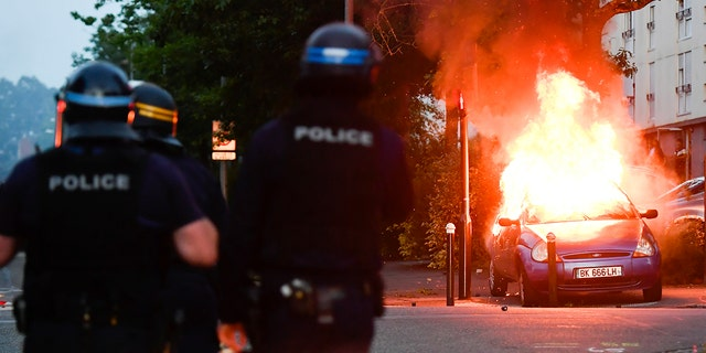 Police officers watch a car burning in Nantes.