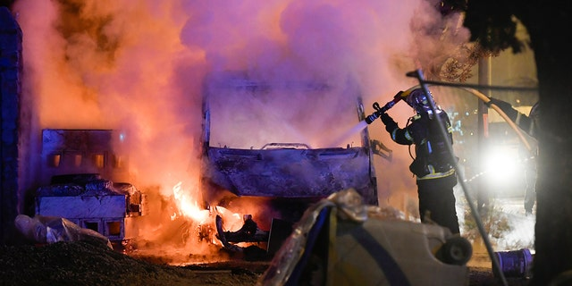 A firefighter works to extinguish a burning vehicle in Nante.