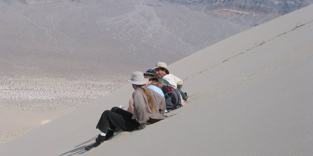 Creating a boom by sliding in unison down the face of a sand dune on the 200 m high Eureka Dune in Death Valley National Park, California.