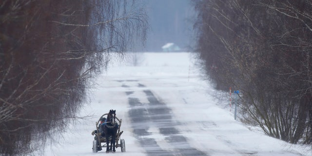People ride on traditional cart through the snow and wind in the village of Podberezhie, 31 miles southeast of Minsk, Belarus, Wednesday, Feb. 28, 2018.