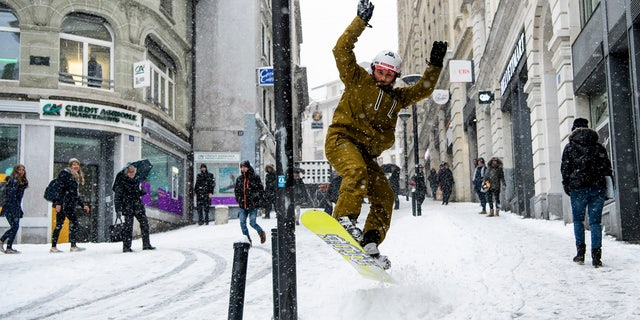 Sylvain rides his snowboard on a snow-covered street during a snowfall in Lausanne, Switzerland, Thursday, March 1, 2018.