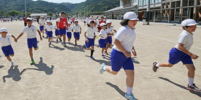 Children and residents conduct an evacuation drill on the assumption that North Korea may launch ballistic missile in Abu, Yamaguchi Prefecture on June 04, 2017