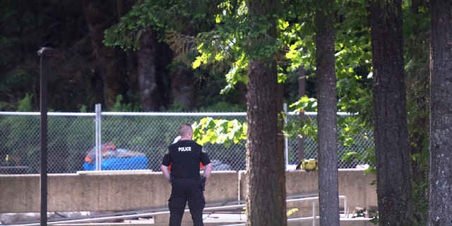 """An Evergreen State College police officers keeps watch over campus as student evacuate following a """"direct threat"""" on Thursday, June 1."""
