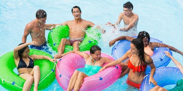 Multi-ethnic group of teens (16 to 18 years) floating on innertubes in swimming pool.