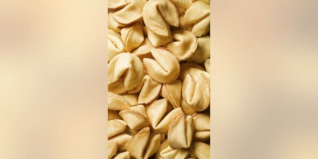 A whole bunch of fortune cookies on a table.