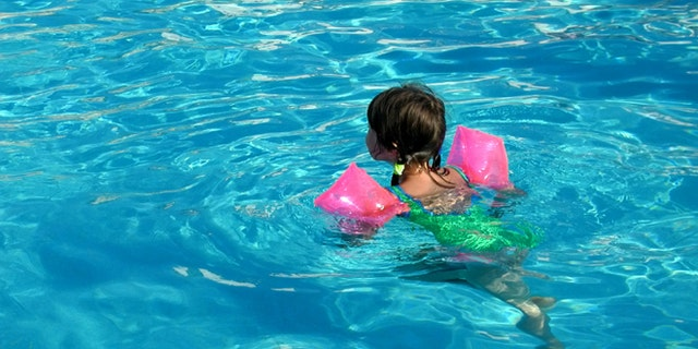 Girl learns to swim by means water wings (also called floaties) in swimming pool.