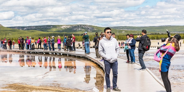 Yellowstone National Park, USA - May 17, 2016: Tourists taking pictures from boardwalk in Grand Prismatic spring in Midway Geyser Basin
