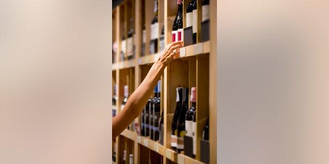 Human hand is buying bottle of wine, selective focus