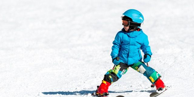 Little boy skiing on mountain