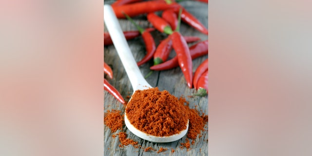 close up of spoon heaped with chilli powder with red chillies in background
