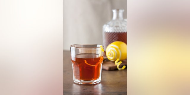 Classic sazerac cocktail with a lemon twist on wooden table