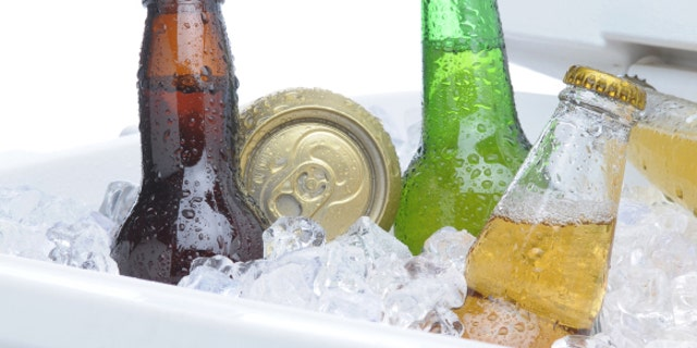 Close up of an assortment of beer bottles and cans in cooler with ice vertical composition