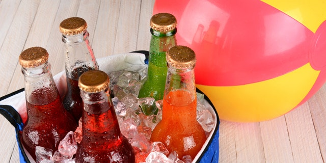 Closeup of a cooler with soda bottles and ice on a rustic wood table with a beachball in the background.