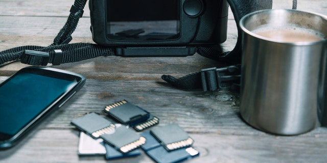 Digital photo camera, memory cards and mobile phone on wooden table