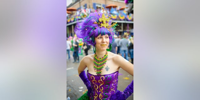 A young woman dressed up on Fat Tuesday on Bourbon Street in New Orleans, LA