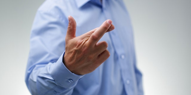 Businessman waiting with fingers crossed wishing for good luck
