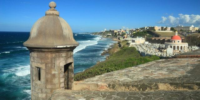 Sentry box overlooking the Atlantic Ocean at 'El Morro' (Castillo San Felipe del Morro) and the La Perla district of Old San Juan, Puerto Rico, including an old cemetery
