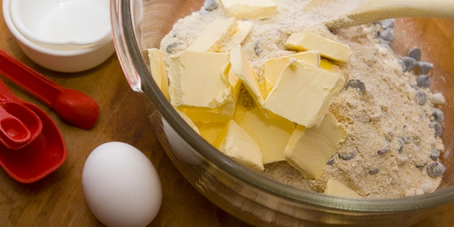 Photo of chocolate chip cookie dough being mixed. Focus is on the butter and egg.