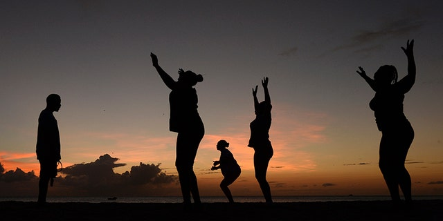 Women exercise in front of a trainer as the sun sets, March 13, 2014.