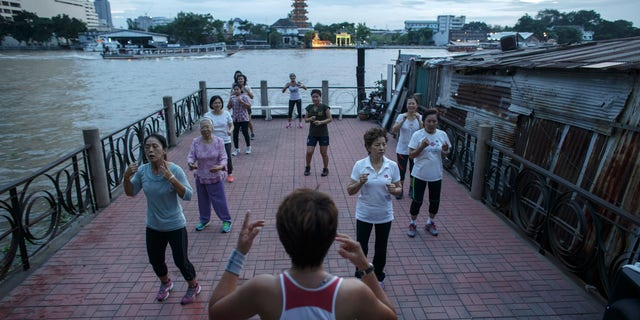 People exercise beside the Chao Phraya river in Bangkok September 24, 2014. Picture taken September 24, 2014. REUTERS/Athit Perawongmetha