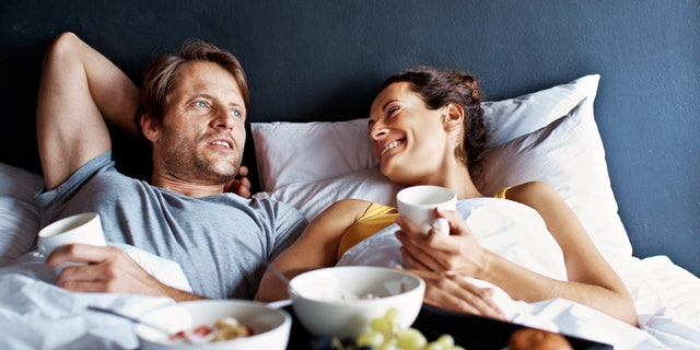 Shot of a mature couple relaxing in bed with breakfast