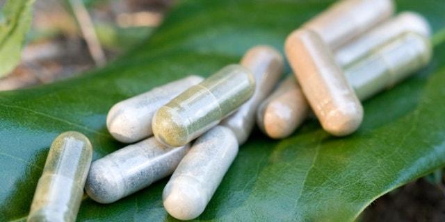 Herbal medicine capsules in a nature environment.