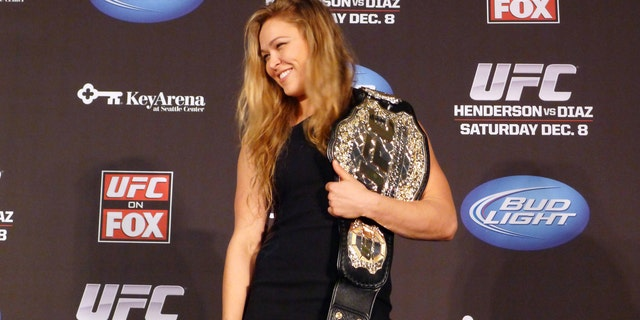 In this Dec. 6, 2012, file photo, mixed martial arts fighter Ronda Rousey shows off her UFC bantamweight championship belt presented to her by UFC president Dana White during a news conference in Seattle. (AP Photo/The Canadian Press, Neil Davidson, File)