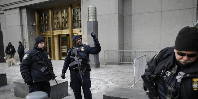 FILE - In this Jan. 22, 2015 file photo, security police watch over the entrance to a federal courthouse in New York where the trial of a man charged with conspiring in the 1998 bombings that killed 224 people at two U.S. embassies in Africa is taking place. Fears over the terror attacks in Paris have raised security at the city's federal courthouses to levels not seen since the days following the Sept. 11, 2001, attacks.  (AP Photo/Seth Wenig, File)