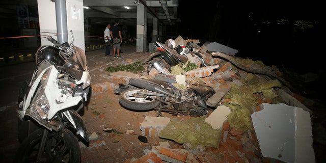 Debris on top of a motorcycles after an earthquake in Bali, Indonesia, Sunday, Aug. 5, 2018.