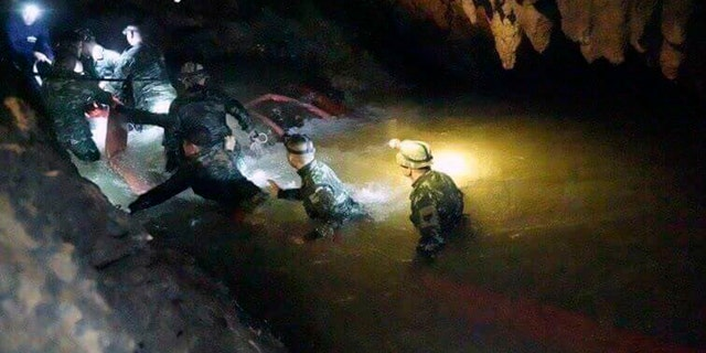 In this handout photo released by Tham Luang Rescue Operation Center, Thai rescue teams walk inside a cave complex in Mae Sai, Chiang Rai province, in northern Thailand, Monday, July 2, 2018.