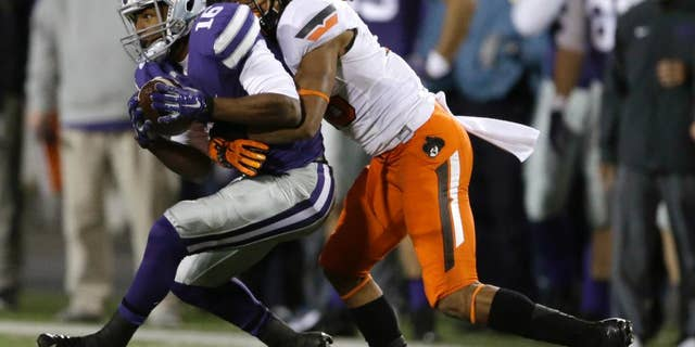 Kansas State wide receiver Tyler Lockett (16) is tackled by Oklahoma State cornerback Ramon Richards (18) during the first half of an NCAA college football game in Manhattan, Kan., Saturday, Nov. 1, 2014. (AP Photo/Orlin Wagner)