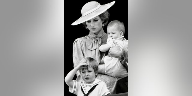 Prince William makes a royal salute as he watches the scene of Trooping the Colour from the balcony of Buckingham Palace with his brother Harry and mother Princess Diana on June 15, 1985 in London.