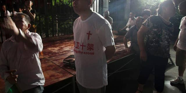 """In this photo taken July 16, 2014, a church member wears a T-shirt with the Chinese words """"Defend the cross"""" as he stakes out overnight to protect the cross from being demolished at a Christian church in Ao'jiang, Pingyang county of Wenzhou in eastern China's Zhejiang province. M(AP Photo/Didi Tang)"""