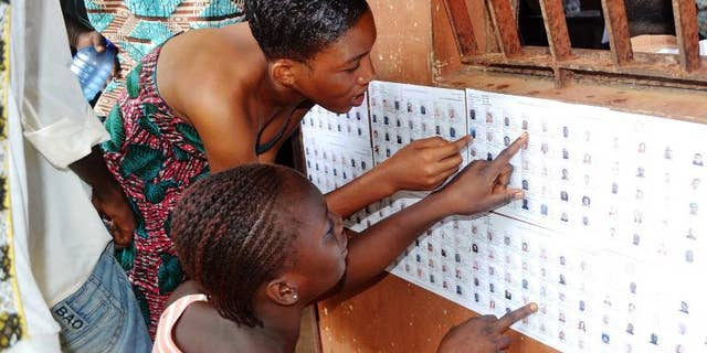 Guinean women search for their names on the registered voters' list at a polling station in Conakry on September 28, 2013
