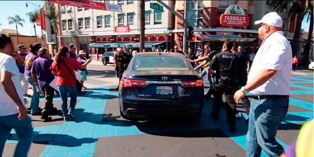 Police arrested the motorist after a car plowed into an immigration rally.