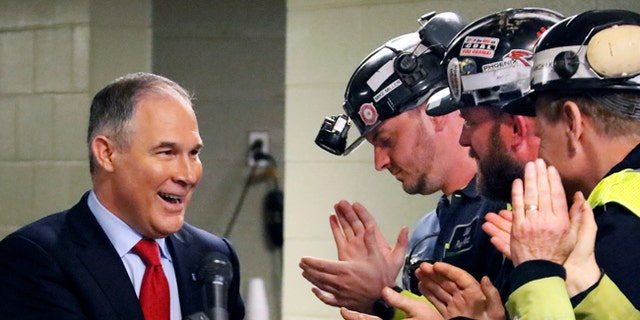 FILE - In this April 13, 2017 file photo Environmental Protection Agency (EPA) Administrator Scott Pruitt, left, shakes hands with coal miners during a visit to Consol Pennsylvania Coal Company's Harvey Mine in Sycamore, Pa. The Trump administration wants to trash Obama-era rules to limit water pollution from coal-fired power plants. Pruitt announced the change this week. Administrator Scott Pruitt sent a letter to a coalition of energy companies that lobbied against the 2015 water pollution rule.  (AP Photo/Gene J. Puskar, File)