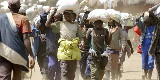 Men carry bags of cassiterite, coltan and computers, and manganese on May 28, 2013 from the Mudere mine, near Rubaya, some 9 kms from the eastern Democratic Republic of Congo city of Goma.