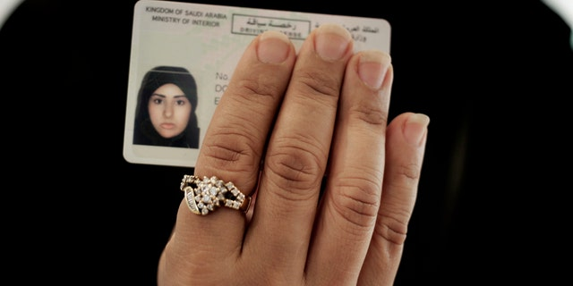 In this June 23, 2018 photo, a Saudi woman covering her name holds her new car license at the Saudi Driving School inside Princess Nora University in Saudi Arabia.