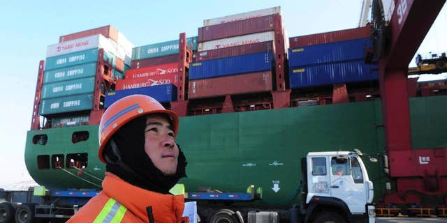 FILE - In this Feb. 15, 2016, file photo, a port worker stands near a container ship at a port in Qingdao in eastern China's Shandong province. Chinese exports have risen for the first time in nine months, in a sign that the outlook may be improving for the world's No. 2 economy. Customs data posted online Wednesday, April 13, 2016, show that China's exports rose 11.5 percent in March compared with a year earlier, to $160.8 billion, after slumping by 25 percent in February. (Chinatopix via AP, File) CHINA OUT